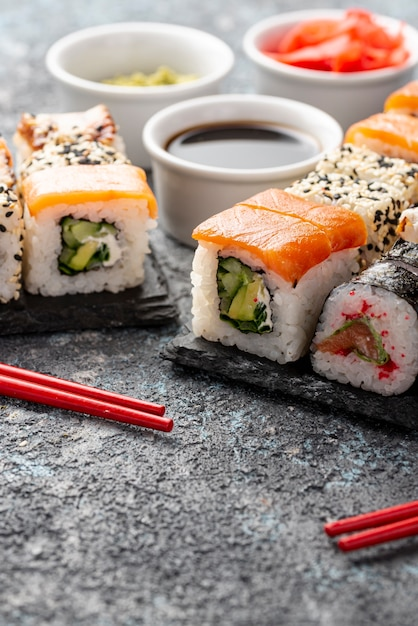 Close-up assortment of maki sushi rolls with chopsticks Free Photo