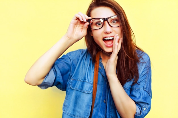 Close-up of astonished girl touching her glasses Free Photo