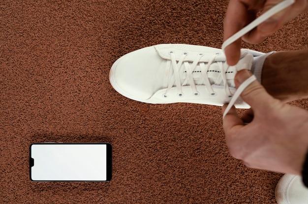 Atleta del primo piano che lega i lacci delle scarpe Foto Gratuite