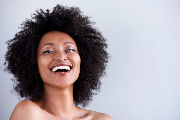 Close up attractive young woman with naked shoulders laughing on gray background Premium Photo
