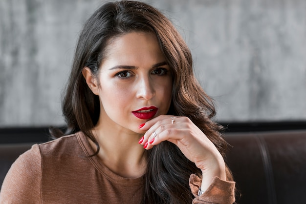 Close-up of an attractive young woman with red lips and nail polish on fingers Free Photo
