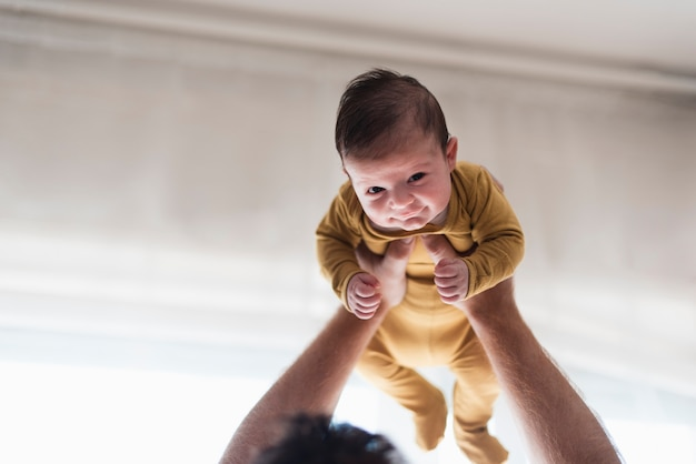 Close-up baby being held up by father Free Photo
