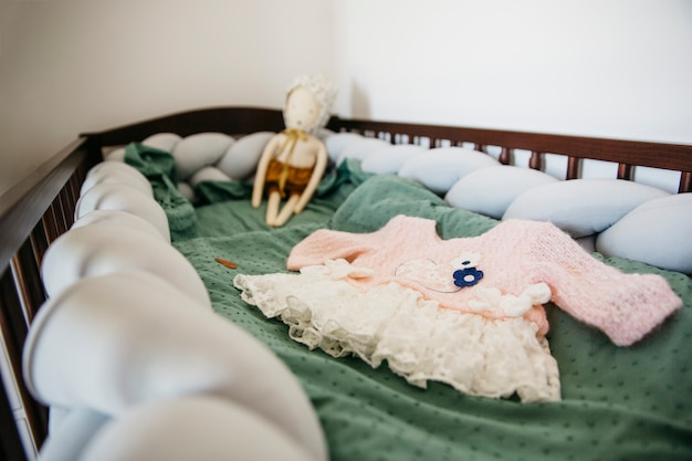 Close-up of baby dress with doll in the crib Free Photo