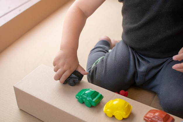 Close up, baby sit and play with the toy car Premium Photo