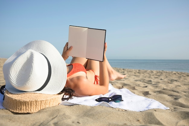 Close up back view woman on beach reading Free Photo