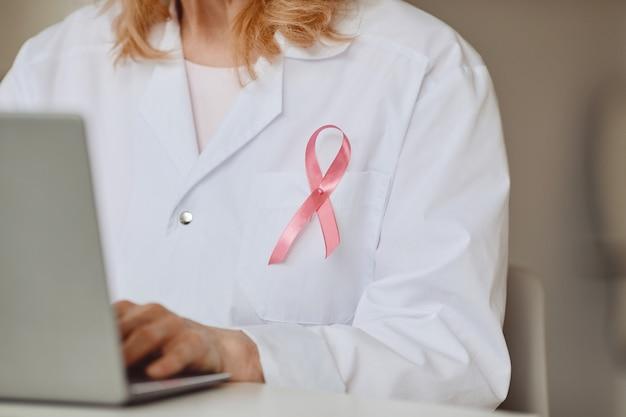 노트북, 유방암 인식 기호, 복사 공간을 사용하는 여성 의사의 흰색 실험실 코트에 고정 된 핑크 리본의 배경을 닫습니다 프리미엄 사진