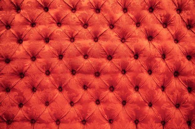 緋色の赤いcapitone本革、レトロなチェスターフィールドスタイルのソフトの背景の質感をクローズアップ Premium写真