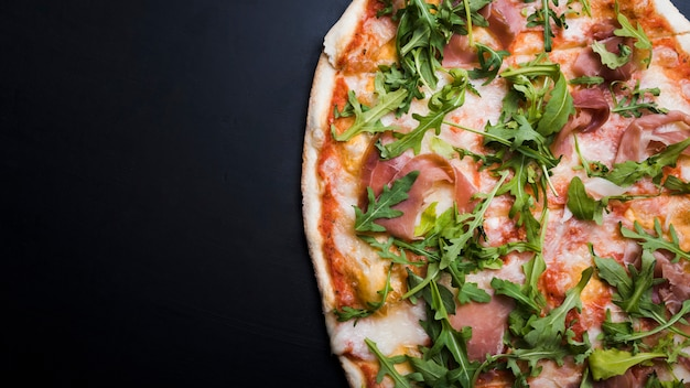 Close-up of bacon and arugula pizza over black surface Free Photo
