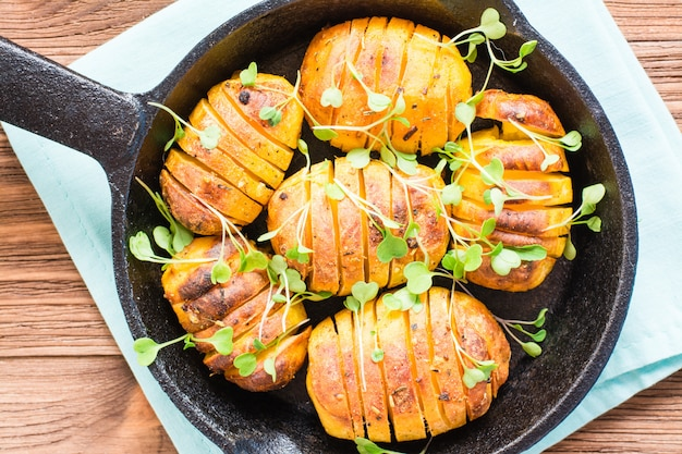Close up of baked young potatoes in spices and oil with arugula in a iron pan on a wooden table. top view Premium Photo