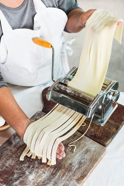 Close-up of baker cutting raw dough into tagliatelle on pasta machine Free Photo