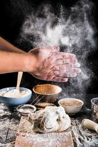 Close-up of baker's hand dusting flour on the dough with ingredients on table Free Photo