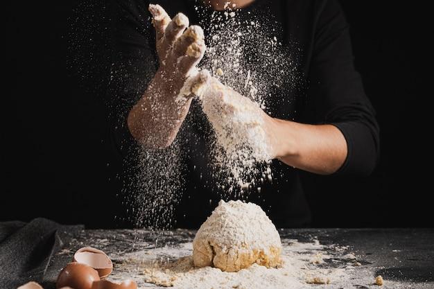 Close-up baker spreading flour on dough Free Photo