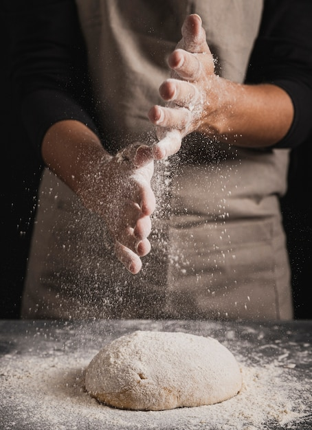 Close-up baker spreading flour on top of dough Free Photo