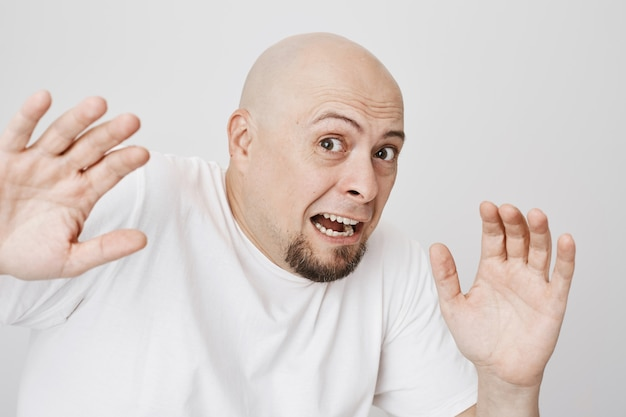 Close-up of bald scared bearded man screaming Free Photo