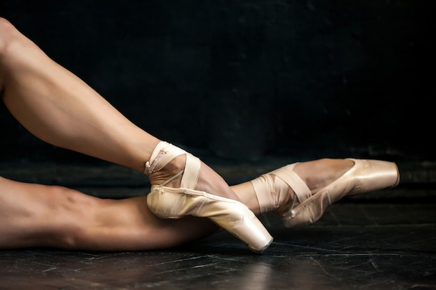 Close-up ballerina's legs in pointes on black wooden floor Free Photo