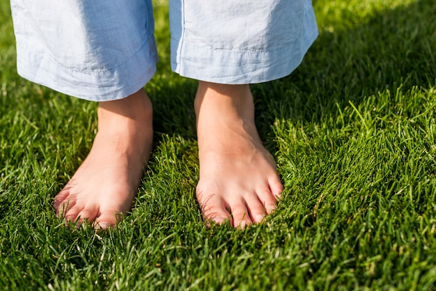 Close-up barefoot girl standing on grass Free Photo