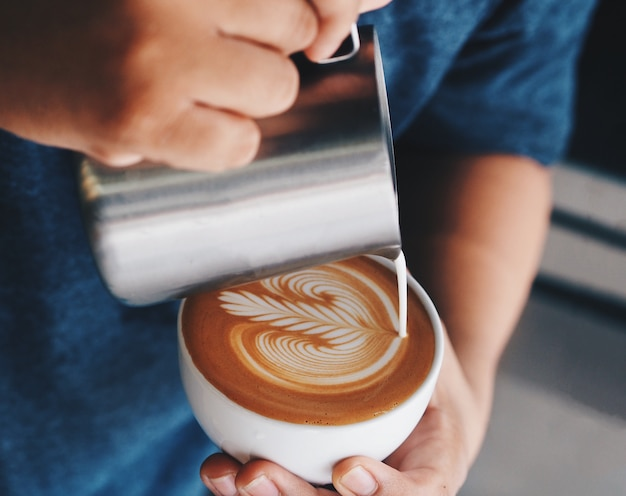 Close up barista hands pouring warm milk in coffee cup for making latte art. Premium Photo