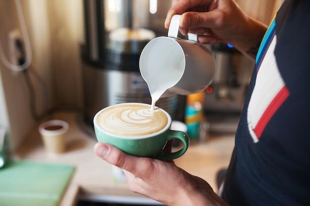 カフェラテアートを作るためにコーヒーカップに暖かい牛乳を注ぐバリスタの手を閉じます。コーヒーショップでプロのコーヒーカフェラテアート。 Premium写真