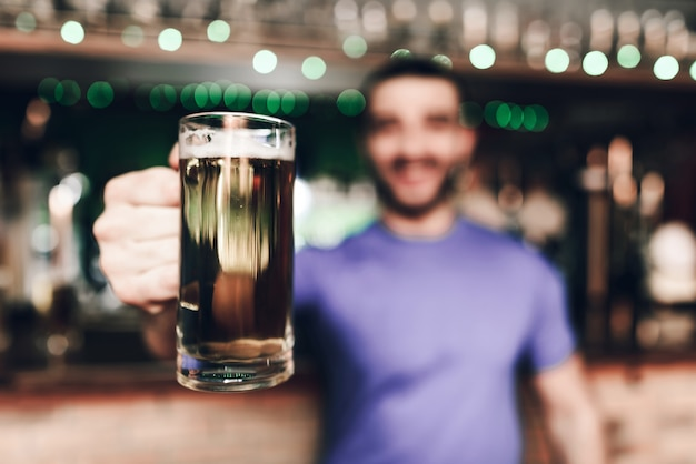 Close up barmen holding glass of beer in bar Premium Photo