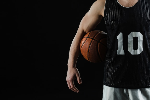 Close-up of basketball player with ball under his arm Free Photo