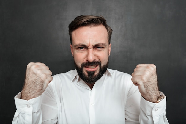 Close up bearded man showing his strength on camera with clenching fists, isolated over dark gray Free Photo