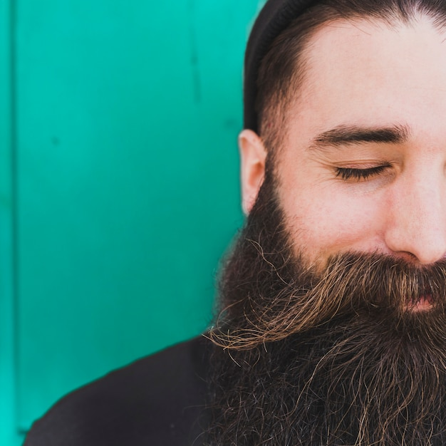 Close-up of bearded man with eye closed against green backdrop Free Photo