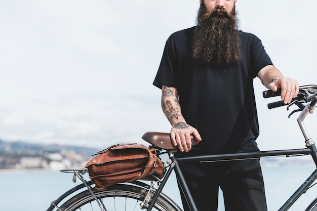 Close-up of bearded young man standing with his bicycle Free Photo