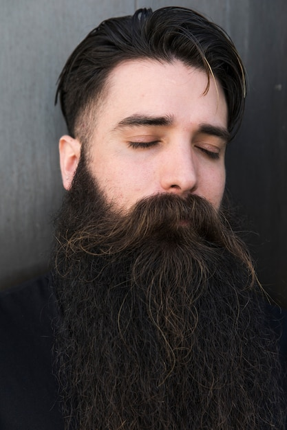 Close-up of bearded young man with eye closed Free Photo