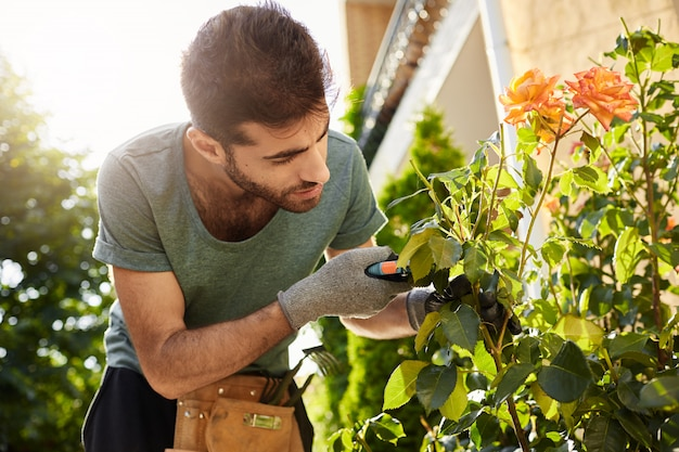 Close up of beautiful bearded florist in blue t-shirt with garden tools cutting dead flowers, spending summer morning in countryside house. Free Photo