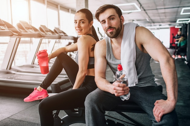 Close up of a beautiful couple sitting on the sport bench and posing. also they are drinking water from their bottles and having rest after hard workout. Premium Photo