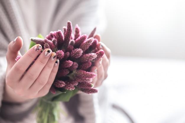 Chiuda su di belle mani femminili che tengono la grande tazza bianca del caffè e dei fiori del cappuccino Foto Gratuite