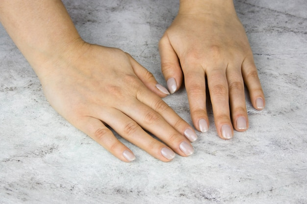 Close up of beautiful female hands with manicure on marble table Premium Photo