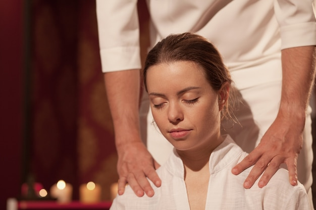 Close up of a beautiful woman enjoying professional thai massage with eyes closed at the spa center. female relaxing while masseur performing traditional thai massage. health, pamper Premium Photo