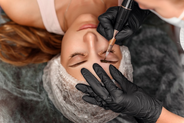 Close up of beautiful woman face with thick brows in beauty salon. permanent makeup for eyebrows. Premium Photo