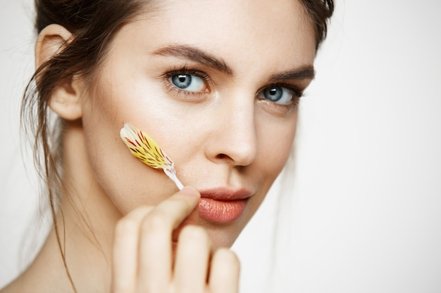 Close up of beautiful young girl with perfect clean skin and alstroemeria petals looking at camera over white background. facial treatment. beauty and spa. Free Photo