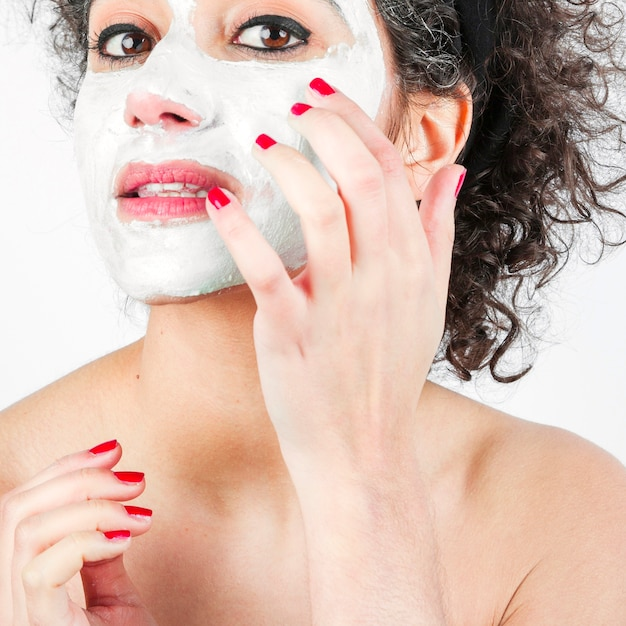 Close-up of beautiful young woman applying white face mask Free Photo