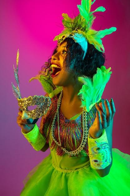 확대. 네온 불빛에 그라데이션 벽에 깃털을 가진 카니발, 세련 된 무도회 의상에서 아름 다운 젊은 여자. 휴일 축하, 축제 시간, 댄스, 파티, 재미의 개념. 무료 사진