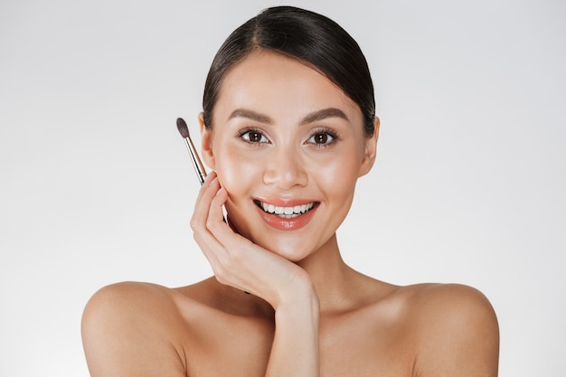 Close up beauty portrait of adorable brunette woman with soft skin holding makeup brush for eyebrows and looking on camera, isolated over white wall Free Photo