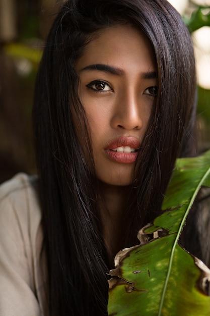 Chiuda sul ritratto di bellezza della donna asiatica con la pelle perfetta che posa nel giardino tropicale. capelli sani, labbra carnose. Foto Gratuite