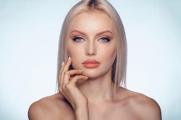 完璧な肌とふっくらした唇と金髪の女性の美しさの肖像画を間近します。 Premium写真
