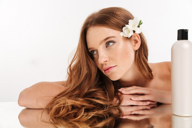 Close up beauty portrait of smiling ginger woman with flower in hair reclines on mirror table with bottle of lotion while looking away Free Photo