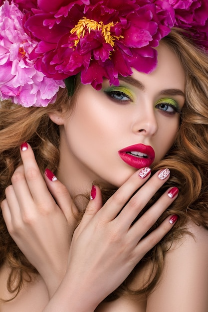 Close-up beauty portrait of young pretty girl with flower wreath in her hair wearing bright pink lipstick and touching her lips. bright modern summer makeup Premium Photo