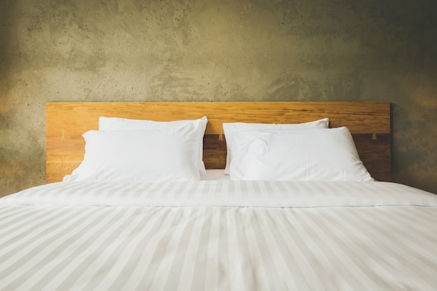 Close up bedroom suite interior with white pillows and wall concrete background Premium Photo