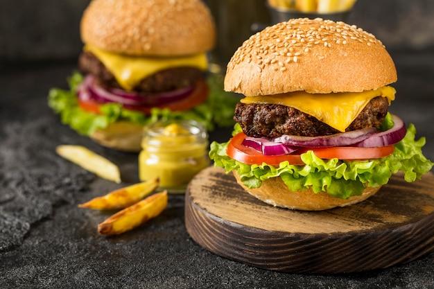 Hamburger di manzo del primo piano sul tagliere con salsa Foto Gratuite