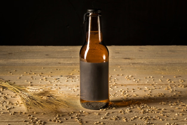 Close-up of a beer bottle and ears of wheat on woodgrain Free Photo