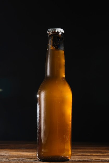 Close-up of a beer bottle on wooden desk Free Photo