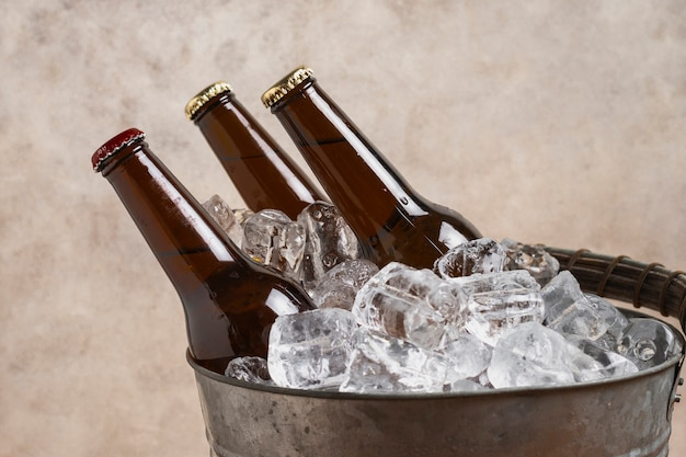 Close-up beer bottles in cold ice cubes Free Photo