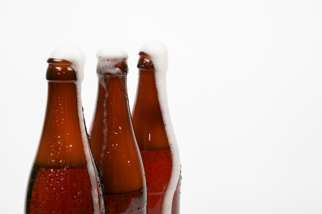 Close up beer bottles with foam and copy space Free Photo