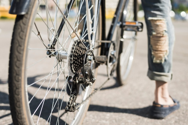 Close-up of bicycle rear wheel with chain & sprocket on road Free Photo