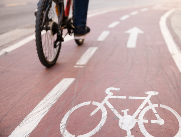 Close-up of bicycle riding the bicycle on the road with bike lane sign Free Photo